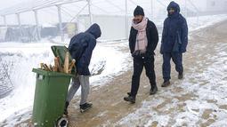 Seorang imigran membawa kayu bakar dalam tempat sampah di Kamp Lipa, luar Bihac, Bosnia, Jumat (8/1/2021). Cuaca bersalju dan musim dingin telah membawa lebih banyak penderitaan bagi ratusan imigran yang terjebak selama berhari-hari di kamp tersebut. (AP Photo/Kemal Softic)