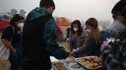 Pengungsi mengambil kue di pusat pengungsian di tempat parkir Walmar, Chico, California (16/11). Departemen Kehutanan dan Perlindungan Kebakaran California mengatakan api telah menghancurkan 40 persen Kota Paradise. (AFP Photo/Justin Sullivan)