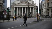 Seorang pria menyeberang jalan pada pagi pertama penerapan lockdown nasional ketiga di Kota London, Inggris, 5 Januari 2021. Inggris memasuki lockdown nasional ketiga sejak pandemi virus corona COVID-19 dimulai. (AP Photo/Matt Dunham)