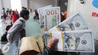 Pengunjung memperlihatkan uang pecahan US$100 di Jakarta, Jumat (9/10/2015). Nilai tukar rupiah terhadap dolar AS pada perdagangan akhir pekan ini, Jumat (9/10/2015) mengalami penguatan, bahkan bergerak ke level Rp 13.400. (Liputan6.com/Angga Yuniar)