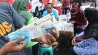 Warga menunjukkan STNK yang baru diperpanjang di gerai Samsat Keliling Car Free Day, Jakarta, Minggu (21/10). Layanan pembayaran pajak Surat Tanda Nomor Kendaraan (STNK) bisa dilakukan tanpa membawa salinan atau BPKB. (Liputan6.com/Angga Yuniar)