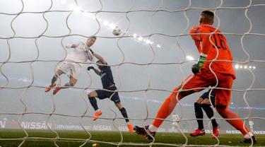 Penyerang Real Madrid Cristiano Ronaldo menyundul bola yang akhirnya berbuah gol saat melawan PSG dalam pertandingan Liga Champions leg kedua di stadion Parc des Princes di Paris (6/3). Madrid berhasil menang 2-1 atas PSG. (AP / Christophe Ena)