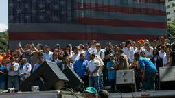 Para pemimpin oposisi Venezuela berdiri di atas panggung berlatar belakang layar raksasa berbendera AS saat demonstran menuntut pengunduran diri Presiden Nicolas Maduro di Caracas, Venezuela, Sabtu (2/2). (AP Photo/Rodrigo Abd)