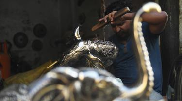 Perajin menyelesaikan kerajinan tangan dari kuningan di sebuah bengkel di Karachi (19/11/2019). Karachi merupakan salah satu pusat kerajinan kuningan terbaik di Pakistan. (AFP Photo/Asif Hassan)