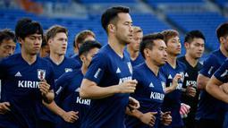 Para pemain Jepang melakukan pemanasan saat sesi latihan di Yokohama, Jepang,  (29/5). Jepang akan menghadapi Ghana pada pertandingan persahabatana jelang bertanding di Piala Dunia 2018.  (AP Photo / Shuji Kajiyama)