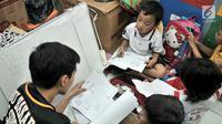 Guru relawan memberikan materi pelajaran kepada anak-anak di Sekolah Komunitas Jendela, Jakarta, Minggu (25/11). Sekolah yang berdiri sejak 2012 dibimbing oleh mahasiswa dan pekerja kantoran. (merdeka.com/Iqbal S. Nugroho)