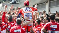 Gaya Andrea Dovizioso (tengah) merayakan kemenangan bersama tim usai balapan MotoGP Austria di Red Bull Ring, Spielberg, Austria (13/8/2017). Dovizioso menjadi juara stelah kalahkan Marquez pada lap terakhir. (AFP/Jure Makovec)