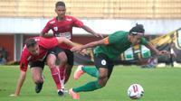 Kapten PSS Sleman, Bagus Nirwanto (hijau) berduel dengan pemain Persipura, Thiago Amaral. (Bola.com/Vincentius Atmaja)