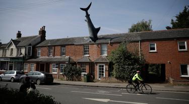 Sebuah patung yang dikenal dengan nama Headington Shark tampak menerobos atap rumah di wilayah pinggiran Oxford, Inggris pada 30 April 2019. Patung hiu unik dibuat tahun 1986 oleh pria asal AS, Bill Heine dari bahan fiberglass dengan panjang 8 meter.  (AP Photo/Matt Dunham)