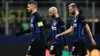Pemain Inter Milan, Mauro Icardi, Borja Valero dan Marcelo Brozovic meninggalkan lapangan usai laga pamungkas penyisihan Grup B Liga Champions melawan PSV Eindhoven di Stadion San Siro, Rabu (12/12). Inter Milan bermain imbang 1-1. (Marco BERTORELLO/AFP)