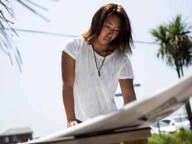 Pesalancar wanita asal Jepang, Minori Kawai mengecek papan selancar saat sesi latihan di kota Ichinomiya, Prefektur Chiba (8/7). Kawai 16 tahun akan berlaga di Olimpiade Tokyo 2020 setelah memenangkan Chiba Open bulan lalu. (AFP Photo/Behrouz Mehri)