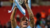 Pemain Manchester City, Danilo mengangkat trofi Piala Liga Inggris seusai mengalahkan Arsenal di Stadion Wembley, Minggu (25/2). Trofi ini sekaligus menjadi trofi pertama yang disumbangkan oleh sang manajer Pep Guardiola. (AP/Tim Ireland)