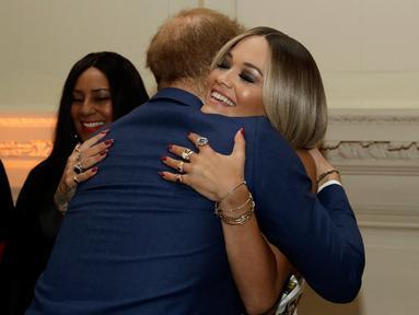 Pangeran Harry memeluk penyanyi Rita Ora sebelum konser yang diadakan badan amal Sentebale di Hampton Court Palace, London (11/6/2019). Konser ini akan mengumpulkan dana dan kesadaran untuk Sentebale, badan amal yang didirikan Pangeran Harry dan Pangeran Lesotho Seeiso 2006. (AP Photo/Matt Dunham)
