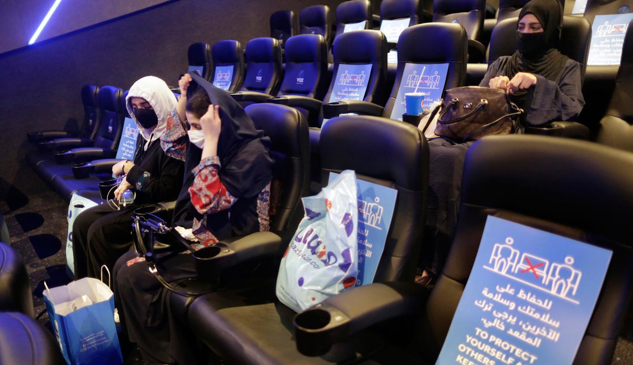 Perempuan Saudi mengenakan masker untuk mencegah penyebaran Covid-19 bersiap menyaksikan film di aula Bioskop VOX di Jiddah, Arab Saudi (26/6/2020). Pemerintah Arab Saudi membuka kembali bioskop setelah melonggarkan lockdown Covid-19. (AP Photo/Amr Nabil)