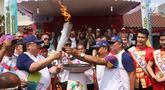 Menteri PPN/Kepala Bappenas Bambang Brodjonegoro (kiri) menyambut Obor Asian Games 2018  dalam Torch Relay atau kirab obor Asian Games di Jakarta Barat di Keluarahan Tanah Sereal, Jakarta Barat, Kamis (16/8).(Liputan6.com/ Herman Zakharia)