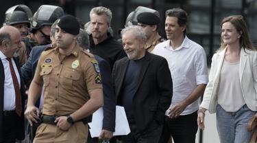 Mantan Presiden Brasil Luiz Inacio Lula da Silva (tengah) tersenyum ketika berjalan keluar dari markas Polisi Federal setelah dipenjara atas tuduhan korupsi di Curitiba, Brasil, (8/11/2019). Luiz Inácio Lula da Silva telah dibebaskan setelah lebih dari 18 bulan dipenjara. (AP Photo/Leo Correa)