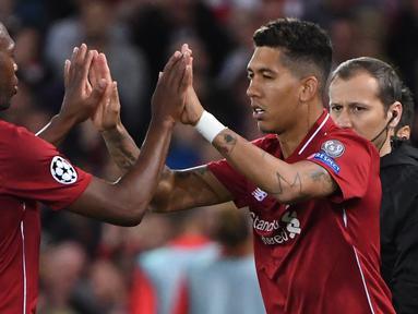 Gelandang Liverpool, Roberto Firmino (kanan) menggantikan Daniel Sturridge saat bertanding dengan Paris Saint-Germain (PSG) di Liga Champions di Anfield, Liverpool, Inggris, Selasa (18/9). Liverpool membungkam PSG 3-2. (Paul ELLIS/AFP)