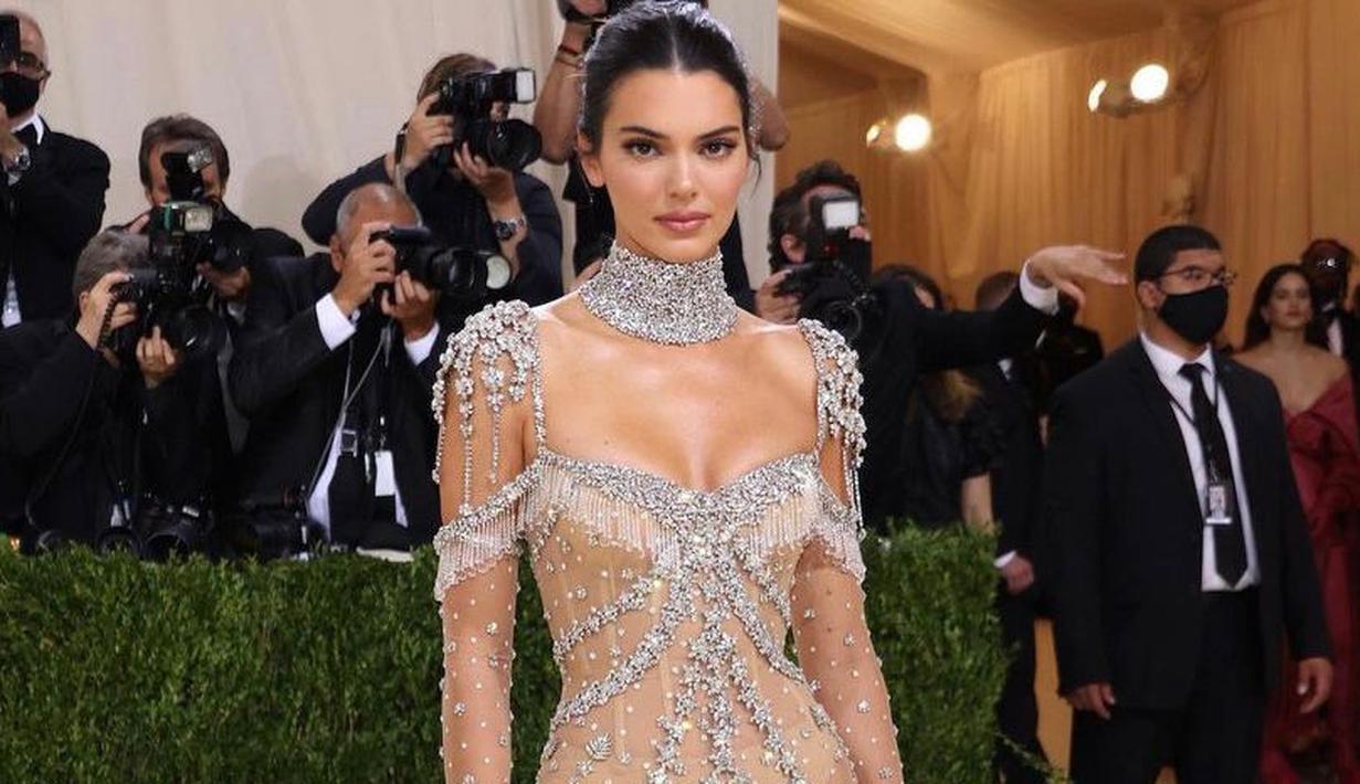 Kendall Jenner tampil bergaya 'naked' dalam balutan sheer gown bertabur kristal berkilau rancangan Givenchy. Penampilannya yang glamor tersebut diperlengkap dengan kalung choker besar. Model 25 tahun ini menjaga rambutnya tetap sederhana dengan sanggul rendah. (Instagram/_metgala2021).