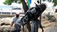 Orang ini gendong motor di pinggir pantai di Bali (Dagelan)