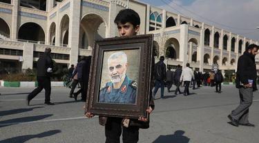 Seorang bocah laki-laki memegang foto Qasem Soleimani dalam acara pemakamannya.