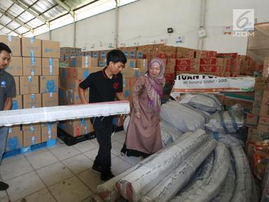 Manager Corporate Affairs JICT Indira Lestari (kanan) menyerahkan bantuan 4 tenda darurat kepada tim ACT di Gudang IHC-ACT Parung, Bogor, Jumat (12/10). Bantuan diperuntukkan kepada korban gempa dan tsunami di Palu dan Donggala. (Liputan6.com/HO/Arif)