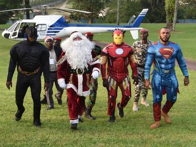 Sejumlah pria mengenakan kostum pahlawan super berjalan di istana kepresidenan di Abidjan, Pantai Gading (23/12). Mereka mengenakan kostum pahlawan super sambil membawa hadiah yang diberikan kepada anak-anak untuk perayaan natal. (AFP Photo/Sia Kambou)