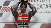 Pembalap Ducati Andrea Dovizioso berpose diatas podium sambil memegang pialanya usai memenangkan balapan di MotoGP Qatar 2018 di Sirkuit Internasional Losail (18/3). (AFP Photo/Karim Jaafar)