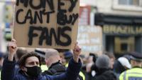 Seorang fans membentangkan poster di luar Stadion Stamford Bridge, London, Selasa (20/4/2021) sebagai protes dibentuknya Liga Super Eropa menjelang laga lanjutan Liga Inggris 2020/2021 pekan ke-32 antara Chelsea melawan Brighton and Hove Albion. (AP/Frank Augstein/Pool)