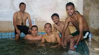 Pemain dan staf Persebaya Surabaya, dari kiri Danang Suryadi (pelatih fisik), Misbakus Solikin, Irfan Jaya, Muhammad Hidayat, dan Alwi Slamat, menikmati berendam setelah laga kontra Persib Bandung. (Bola.com/Aditya Wany)