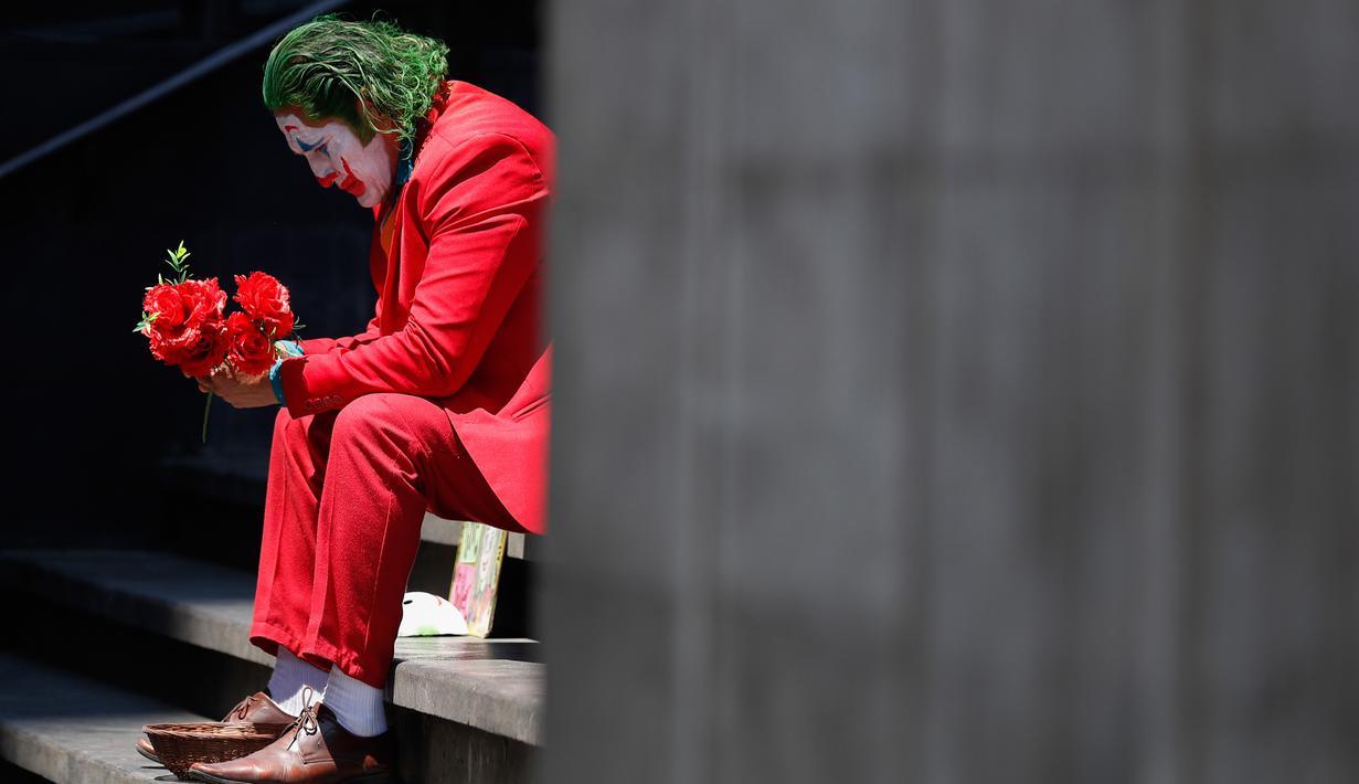 David Vazquez, seniman jalanan berpakaian seperti Joker menunggu dengan harapan pejalan kaki akan membayar berfoto dengannya di Mexico City (23/3/2020). Meluasnya penyebaran COVID-19, membuat warga canggung untuk berfoto dengan Vazquez yang merupakan pelatih di gym. (AP Photo/Rebecca Blackwell)