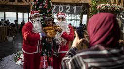 Pramusaji Palestina berpakaian Sinterklas menggendong seorang anak untuk berfoto di sebuah restoran di pantai di Kota Gaza, Minggu (13/12/2020). REstoran tersebut didandani dengan tema Natal, pelayanannya pun berpakaian seperti Sinterklas. (AP Photo/Khalil Hamra)