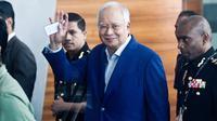Mantan Perdana Menteri Najib Razak melambaikan tangan setibanya di kantor Komisi Anti-Korupsi Malaysia (MACC), Putrajaya, Selasa (22/5). Najib hari ini menjalani pemeriksaan terkait kasus korupsi 1Malaysia Development Berhad (1MDB). (AP/Sadiq Asyraf)