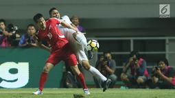 Pemain belakang Indonesia U-23, Ricky Fajrin S (kanan) berebut bola dengan pemain Korea Utara, Jo Sol Song pada laga PSSI Anniversary Cup 2018 di Stadion Pakansari, Kab Bogor, Senin (30/4). Babak pertama imbang 0-0. (Liputan6.com/Helmi Fithriansyah)