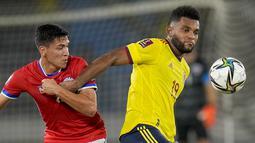 Gelandang Chile Macelino Nunez dan penyerang Kolombia Miguel Borja berebut bola pada lanjutan Kualifikasi Piala Dunia 2022 zona Amerika Selatan di Estadio Metropolitano Roberto Meléndez, Jumat (10/9/2021). Dua gol Miguel Borja memastikan Kolombia menang 3-1 atas Chile.  (AP/Fernando Vergara)
