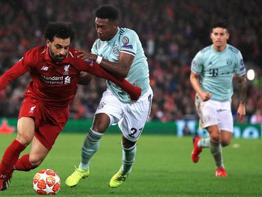 Penyerang Liverpool Mohamed Salah (kiri) berebut bola dengan pemain Bayern Munchen David Alaba pada leg pertama babak 16 besar Liga Champions di Anfield, Liverpool, Inggris, Selasa (19/2). Pertandingan berakhir 0-0. (Peter Byrne/PA Wire/PA via AP)