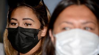 Leia Se, perempuan asal Rusia (kiri) menghadiri konferensi pers sebelum dideportasi di kantor Kemenkumham Bali, Rabu (5/5/2021). Leia Se diamankan pihak imigrasi karena membuat konten prank melukis wajah mirip masker di Bali akhirnya dideportasi. (AFP/Sonny Tumbelaka)