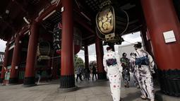 Pengunjung mengenakan kimono berjalan-jalan di distrik Asakusa  di Tokyo, Selasa (29/9/2020). kota Jepang mengonfirmasi lebih dari 200 kasus virus corona pada hari Selasa. (AP Photo/Eugene Hoshiko)