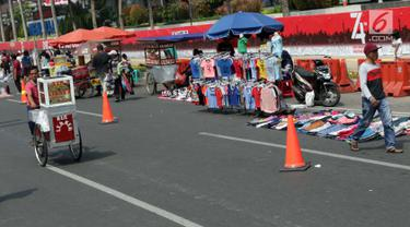 Pedagang kaki lima (PKL) menggelar dagangannya di Jalan Jenderal Sudirman saat Hari Bebas Kendaraan, Jakarta, Minggu (25/8/2019). Para PKL ini menggelar dagangannya terlalu menjorok ke tengah jalan sehingga mengganggu kenyamanan warga yang berolahraga saat CFD. (Liputan6.com/Helmi Fithriansyah)