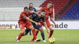 Penyerang Lyon, Mathis Cherki, berebut bola dengan pemain Nimes pada laga lanjutan Liga Prancis di Stadion Groupama, Sabtu (19/9/2020) dini hari WIB. Lyon bermain imbang 0-0 atas Nimes. (AP Photo/Laurent Cipriani)