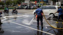 Sejumlah personil pemadam kebakaran membersihkan tumpah oli yang terjadi di Jalan Veteran depan Gedung Krida Bakti, Jakarta, Kamis (16/1/2020). Petugas damkar  melakukan pembersihan dengan cairan deterjen maupun campuran khusus agar jalan tersebut tidak lagi licin. (Liputan6.com/Faizal Fanani)