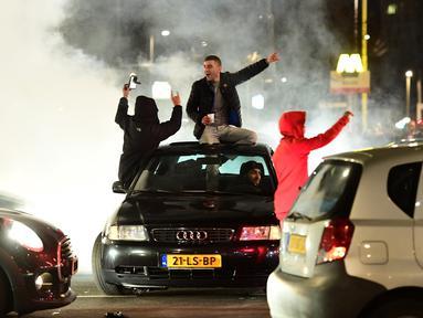 Warga Turki berkumpul menggelar protes di Rotterdam, Belanda (11/3). Aksi protes dilancarkan setelah Pemerintah Belanda melarang Menteri Luar Negeri Turki mendarat di Belanda. (AFP/Emmanuel Dunand)