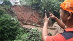 Warga mengambil foto longsor yang terjadi di kawasan Ciganjur, Jakarta Selatan, Senin (13/11).  Longsor diduga akibat penumpukan material pembangunan serta hujan deras yang mengguyur Jakarta. (Liputan6.com/Immanuel Antonius)