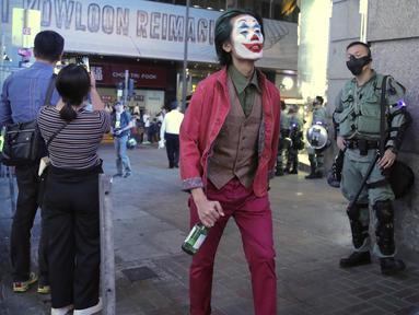 Seorang pria dengan kostum Halloween berjalan melewati petugas polisi di Hong Kong, Kamis (31/10/2019). Para pemrotes Hong Kong menyerukan kepada orang-orang untuk merayakan Halloween dengan mengenakan topeng yang menggambarkan pejabat pemerintah atau tokoh-tokoh menakutkan. (AP Photo/Kin Cheung)
