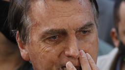 Presiden Brasil Jair Bolsonaro berbicara kepada wartawan saat meninggalkan rumah sakit di Sao Paulo, Minggu (18/7/2021). Pihak rumah sakit sebelumnya mengatakan Bolsonaro akan tetap berada di bawah observasi sebagai pasien meski sudah tidak lagi menjalani rawat inap. (AP Photo/Nelson Antoine)