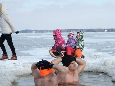 Anak-anak berkereta luncur melewati penggemar renang es di Danau Zalew Zegrzynski di Nieporet, Polandia, Minggu (25/2). Gelombang dingin sedang melanda Polandia. (AP Photo/Alik Keplicz)