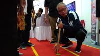 Deputi III Pembudayaan Olahraga Kemenpora, Raden Isnanta saat mencoba olahraga tradisional Balogo di Pameran Haornas (istimewa)