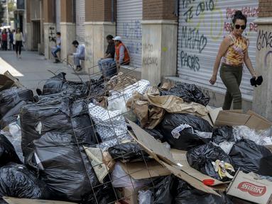 Seorang wanita berjalan melewati tumpukan sampah akibat pemogokan petugas sampah di Santiago (14/11/2019). Protes kekerasan meletus di ibukota Chile, Santiago, pada Selasa ketika mata uang negara itu turun ke level terendah dalam sejarah. (AFP/Javier Torres)