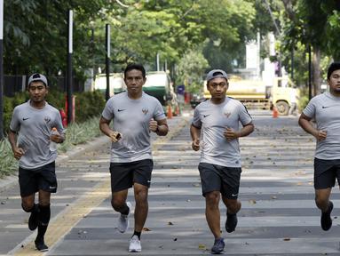 Pelatih Timnas Indonesia, Bima Sakti, bersama staf pelatihnya jogging menuju penginapan usai latihan di Stadion Madya Senayan, Jakarta, Rabu (21/11). Kebiasaan ini sering dilakukan sejak era Luis Milla. (Bola.com/M. Iqbal Ichsan)