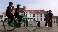 Anak-anak mengenakan masker menggunakan sepeda wisata di kawasan Kota Tua Jakarta, Kamis (29/10/2020). Libur panjang di masa pemberlakuan PSBB transisi Jakarta dimanfaatkan warga untuk mengunjungi lokasi-lokasi wiisata. (Liputan6.com/Helmi Fithriansyah)