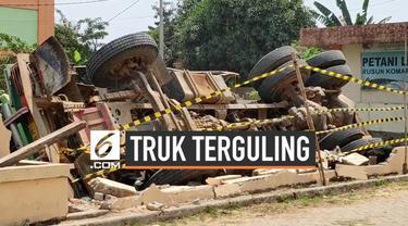 Sebuah truk Fuso terguling kedalam kolam di kawasan Cakung, Jakarta Timur.